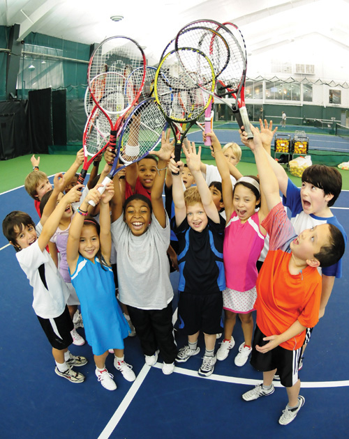 Happy kids holding tennis rackets in the air